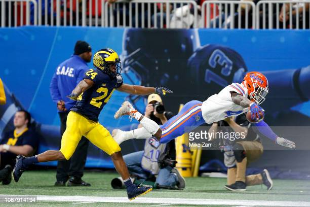 Kadarius Toney of the Florida Gators dives for extra yards while being pursued by Lavert Hill of the Michigan Wolverines in the third quarter during...