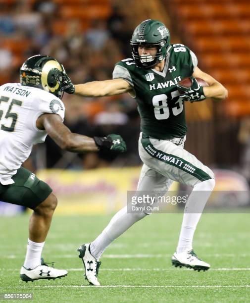 Kade Greeley of the Hawaii Rainbow Warriors keeps Josh Watson of the Colorado State Rams at arms length as he run the ball after making a catch...