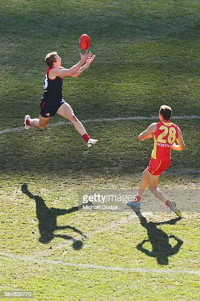 Kade Kolodjashnij of the Suns collides into James Harmes of the Demons after he marks the ball during the round 19 AFL match between the Melbourne...
