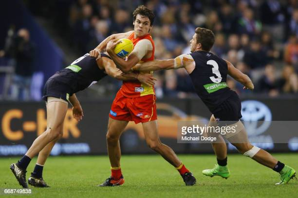 Kade Kolodjashnij of the Suns gets tackled by Kade Simpson of the Blues and Marc Murphy of the Blues during the round four AFL match between the...