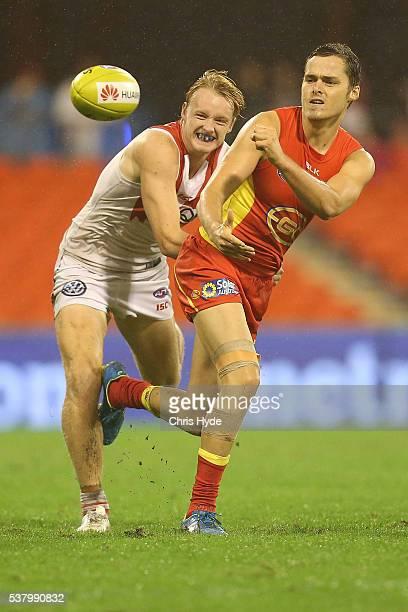 Kade Kolodjashnij of the Suns handballs during the round 11 AFL match between the Gold Coast Suns and the Sydney Swans at Metricon Stadium on June 4...