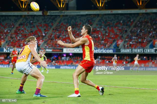 Kade Kolodjashnij of the suns handballs during the round one AFL match between the Gold Coast Suns and the Brisbane Lions at Metricon Stadium on...