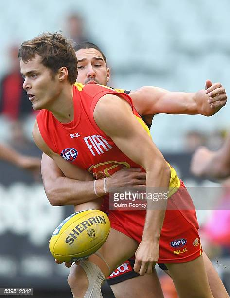 Kade Kolodjashnij of the Suns handballs whilst being tackled by Shaun Grigg of the Tigers during the round 12 AFL match between the Richmond Tigers...