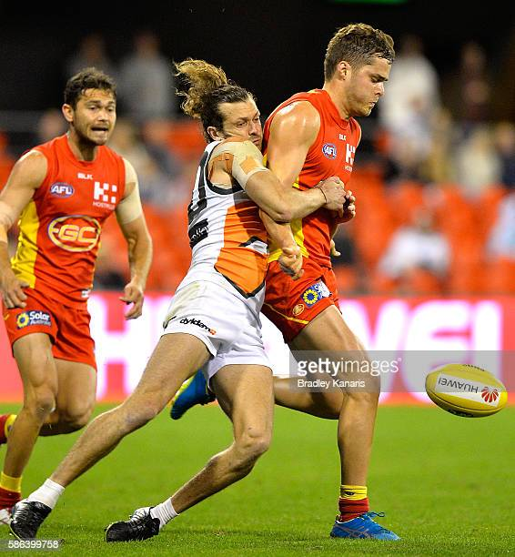 Kade Kolodjashnij of the Suns is pressured by the defence of Sam J Ried of the Giants during the round 20 AFL match between the Gold Coast Suns and...
