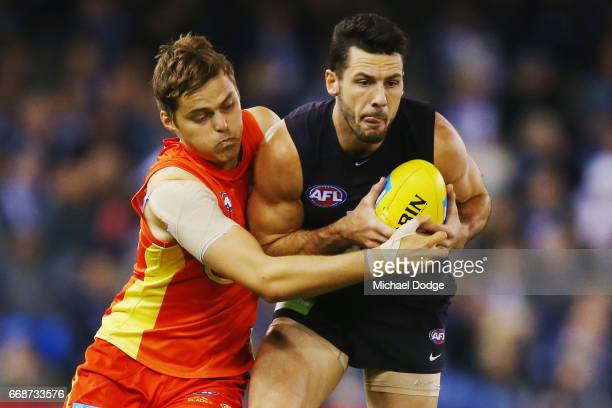Kade Kolodjashnij of the Suns tackles Simon White of the Blues during the round four AFL match between the Carlton Blues and the Gold Coast Suns at...