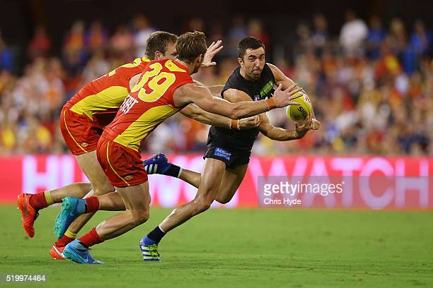 Kade Simpson of the Blues handballs during the round three AFL match between the Gold Coast Suns and the Carlton Blues at Metricon Stadium on April 9...