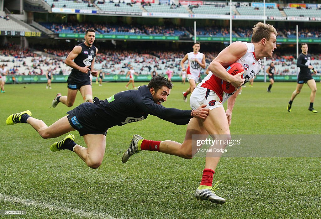 Kade Simpson of the Blues tackles Aaron Vandenberg of the Demons during the round 22 AFL match between the Carlton Blues and the Melbourne Demons at Melbourne Cricket Ground on August 21, 2016 in Melbourne, Australia.