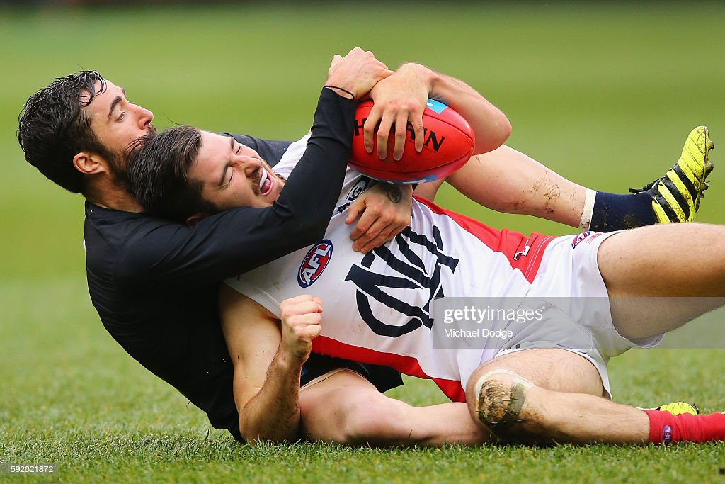 Kade Simpson of the Blues tackles Alex Neal-Bullen of the Demons during the round 22 AFL match between the Carlton Blues and the Melbourne Demons at Melbourne Cricket Ground on August 21, 2016 in Melbourne, Australia.