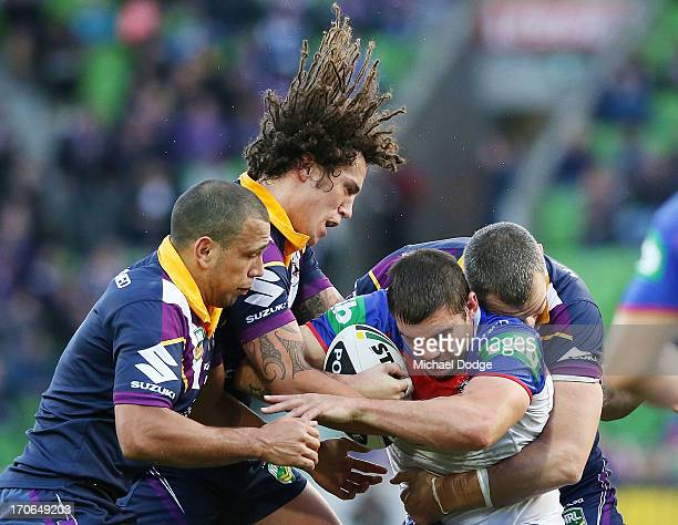 Kade Snowden of the Knights gets tackled by Kevin Proctor and Ryan Hinchcliffe of the Storm during the round 14 NRL match between the Melbourne Storm...