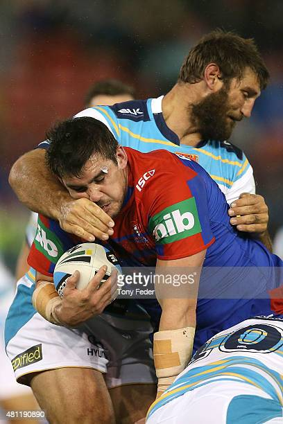Kade Snowden of the Knights is tackled by Dave Taylor of the Titans during the round 19 NRL match between the Newcastle Knights and the Gold Coast...