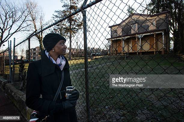 Kadija A. Bangura stands in front of decaying homes in the 2200 block of Martin Luther King Avenue in Washington, DC on January 17, 2014. The parcel,...
