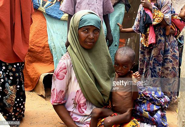 Kadijo Suleyman an internally displaced person from southern Somalia holds her malnourished child in front of her makeshift shelter on August 25 at...