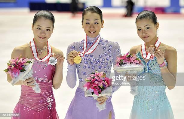 Kadoma, Japan - Akiko Suzuki, Mao Asada and Kanako Murakami hold their silver, gold and bronze medals after the figure skating national championships...
