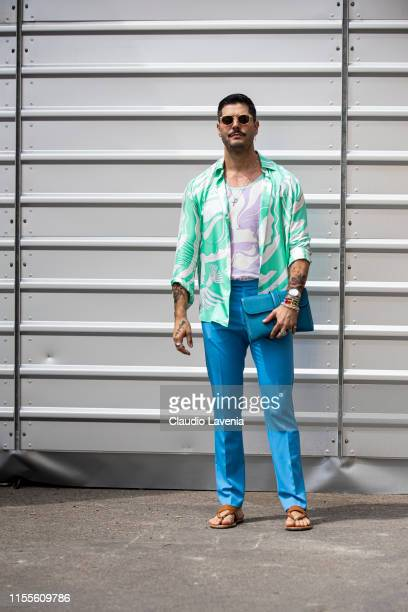 Kadu Dantas wearing a printed white and lilac tshirt printed white and green shirt light blue pants blue bag and brown sandals is seen during Pitti...