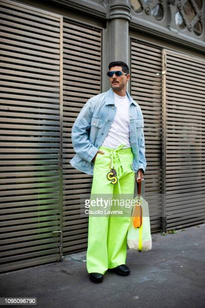 Kadu Dantas wearing a white tshirt neon green pants denim jacket and colorful bag is seen in the streets of Paris before the Acne Studio show on...