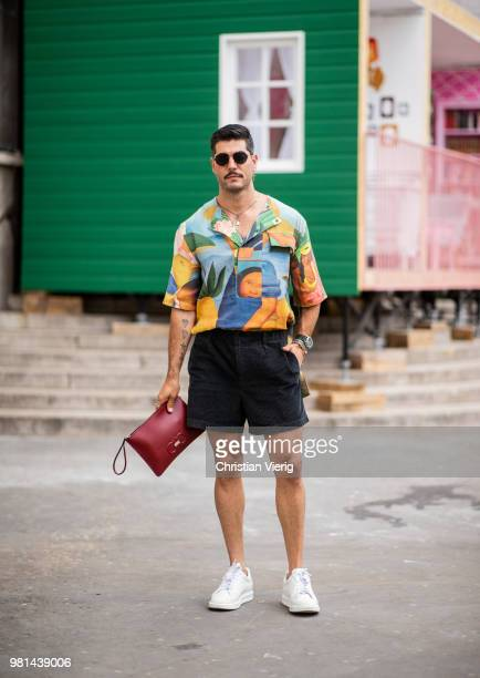 Kadu Dantas wearing shorts clutch button shirt with graphic print is seen outside Ann Demeulemeester on day four of Paris Fashion Week Menswear SS19...