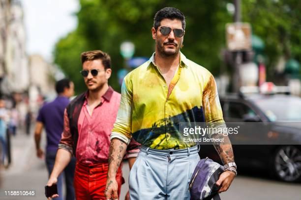 Kadu Dantas wears sunglasses, a colorful watercolor shirt, pale blue leather pants, a purple watercolor bag , outside Paul Smith, during Paris...