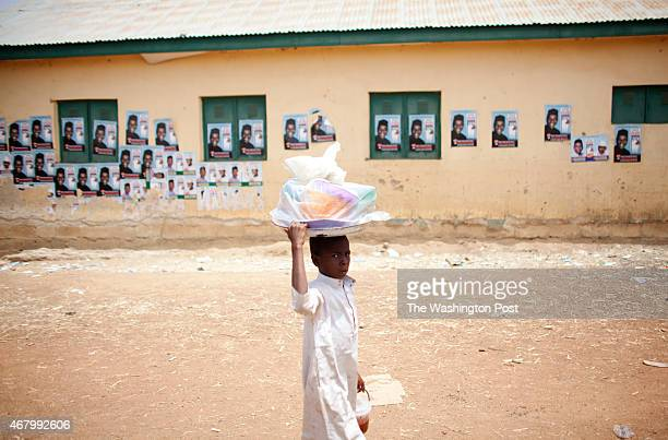 A boy walks passed APC opposition posters at the LEA Primary School in the Danbushia Community as election officials are over three hours late to...