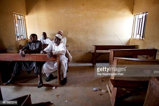 Men wait in a classroom at the Nurul Islam Primary School in the Danbushia Community as election officials are over three hours late to arrive with...