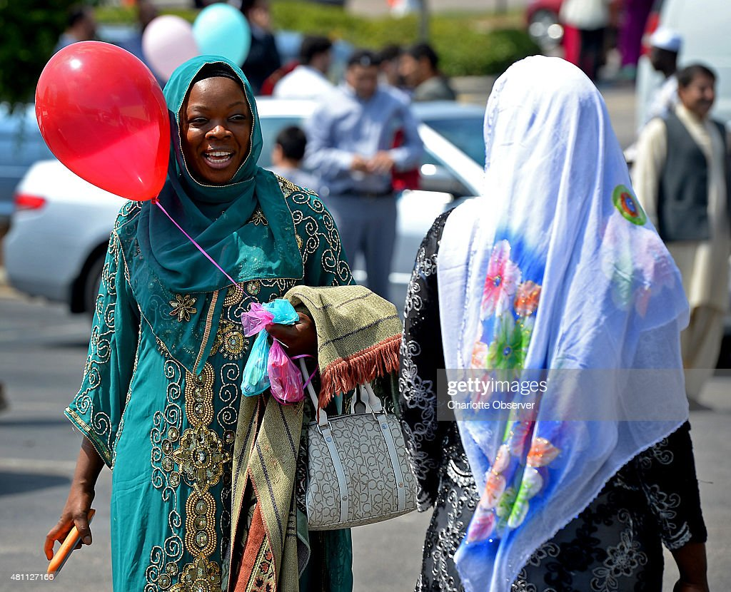 Kady Drame, left, exchanges greetings with another woman on Friday, July 17, 2015 as she joined thousands of Charlotte-area Muslims gathered to mark the end of Ramadan with prayer and greetings of 'Eid Mubarak,' which is Arabic for 'Happy Eid,' at the Cabarrus Arena in Concord, N.C. Eid al-Fitr is a holiday that ushers in three days of communal meals and gift-giving. It directly follows Ramadan, a holy month of fasting and repentance and the most sacred time on the Islamic calendar.