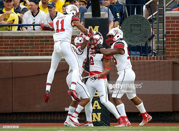 Kaelin Clay of the Utah Utes celebrates a second quarter touchdown with Troy McCormick,Sharrieff Shah Jr. #59 and Davion Orphey while playing the...