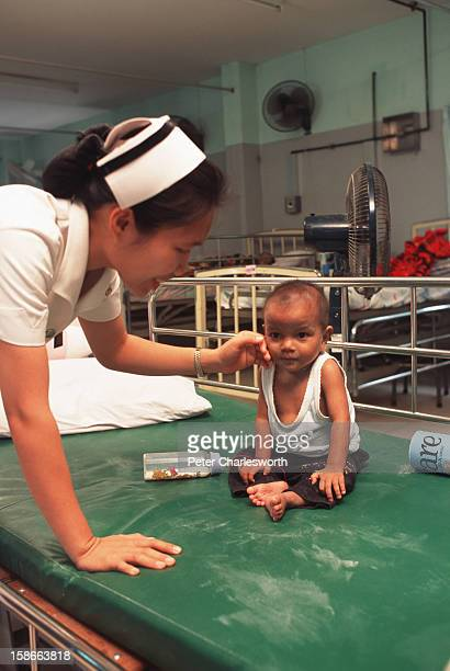 Kaesarin Lukgaid a fourteen month old orphan being looked after by nurse Thanyaporn Kunsombat in the hospital at the Buddhist Temple called Wat Pra...