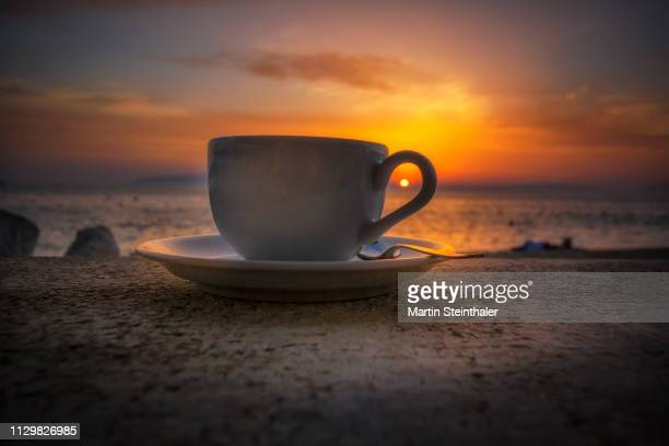kaffeetasse und sonnenuntergang am meer - lebensstil stock photos and pictures