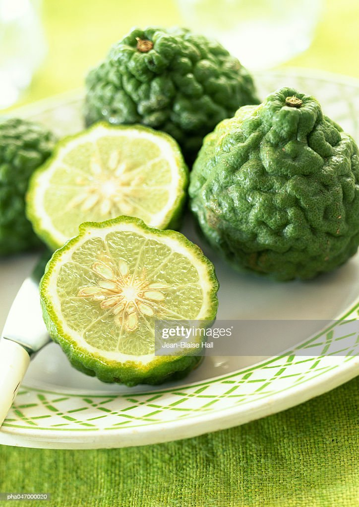 Kaffir limes, one cut in halves, on plate, close-up : Stockfoto