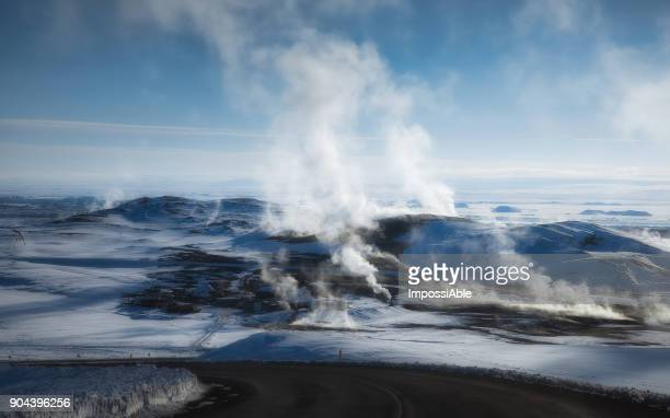 Kafla thermal energy with smoke from the crater above the lava field covered by snow in winter