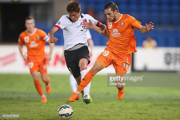 Kaga Kenichi of the Red Diamonds and Jack Hingert of the Roar compete for the ball during the Asian Champions League match between the Brisbane Roar...
