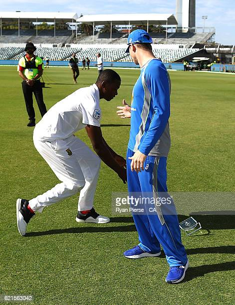 Kagiso Rabada of South Africa drops his Man of the Match trophy as he is congratulated by Steve Smith of Australia after day five of the First Test...