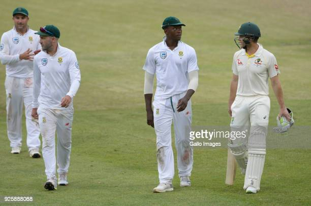 Kagiso Rabada of the Proteas speaks to Tim Paine of Australia after bad light stopped play during day 1 of the 1st Sunfoil Test match between South...
