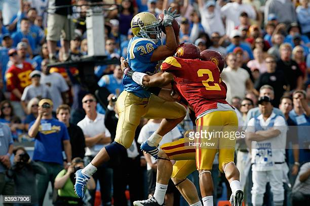 Kahlil Bell of the UCLA Bruins catches a pass for touchdown over Clay Matthews and Taylor Mays of the USC Trojans in the first quarter on December 6,...