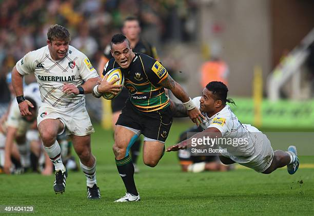 Kahn Fotuali'i of Northampton Saints breaks through the tackle of Manu Tuilagi and Tom Youngs of Leicester Tigers during the Aviva Premiership Semi...
