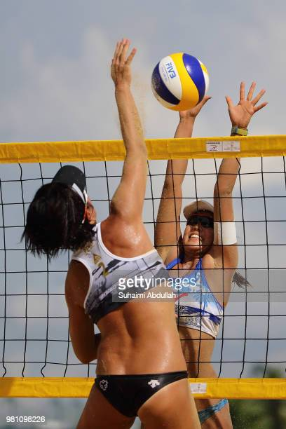Takemi Nishibori of Japan attempts to block Yukano Suzuki of Japan spikes during the main draw pool E women's match on day one of the FIVB Beach...
