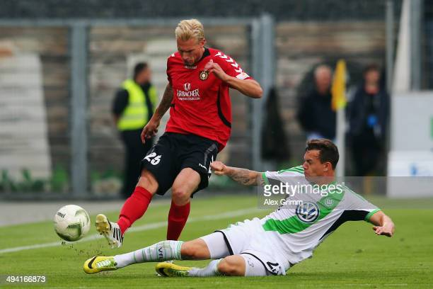 Kai Gehring of Grossaspach is challenged by Kevin Scheidhauer of Wolfsburg during the Third Bundesliga Playoff first leg match between SG Sonnenhof...