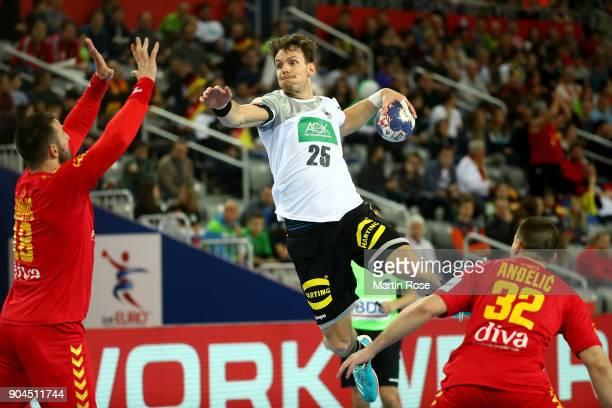 Kai Haefner of Germany challenges Nebosja Simovic of Montenegro during the Men's Handball European Championship Group C match between Germany and...