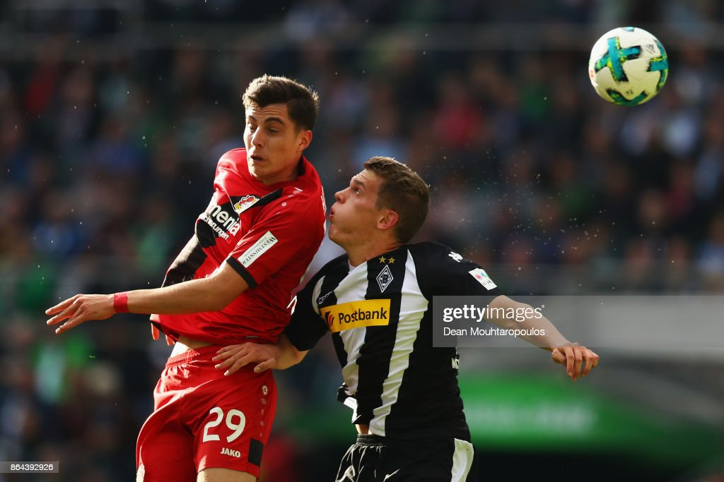 Kai Havertz of Bayer 04 Leverkusen battles for the ball with Matthias Ginter of Borussia Monchengladbach during the Bundesliga match between Borussia Moenchengladbach and Bayer 04 Leverkusen at Borussia-Park on October 21, 2017 in Moenchengladbach, Germany.