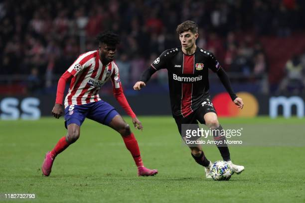 Kai Havertz of Bayer Leverkusen competes for the ball with Thomas Teye Partey of Atletico de Madrid during the UEFA Champions League group D match...