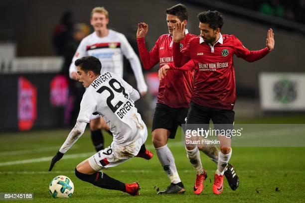 Kai Havertz of Bayer Leverkusen falls next to Julian Korb of Hannover 96 and Edgar Prib of Hannover 96 during the Bundesliga match between Hannover...