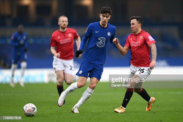 Kai Havertz of Chelsea is challenged by John O'Sullivan of Morecambe during the FA Cup Third Round match between Chelsea and Morecambe at Stamford...