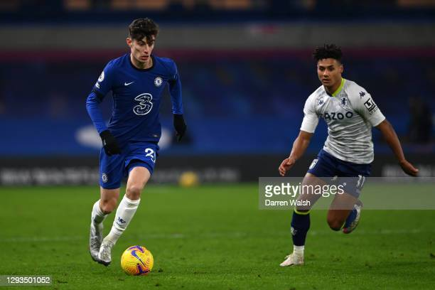 Kai Havertz of Chelsea runs with the ball as he is closed down by Ollie Watkins of Aston Villa during the Premier League match between Chelsea and...