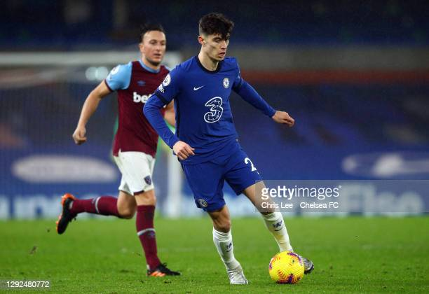 Kai Havertz of Chelsea runs with the ball past Mark Noble of West Ham United during the Premier League match between Chelsea and West Ham United at...