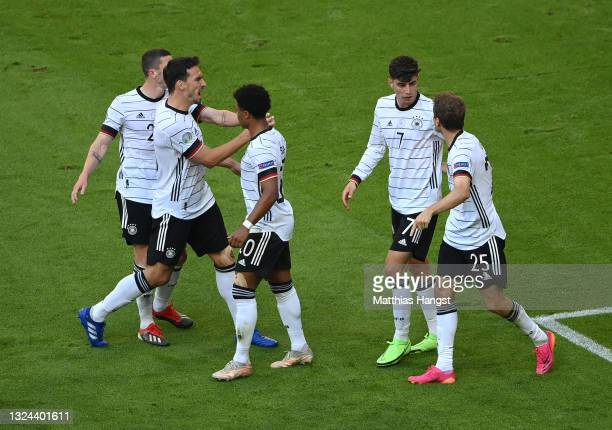 Kai Havertz of Germany celebrates with team mates after their side's first goal credited as an own goal scored by Ruben Dias of Portugal during the...