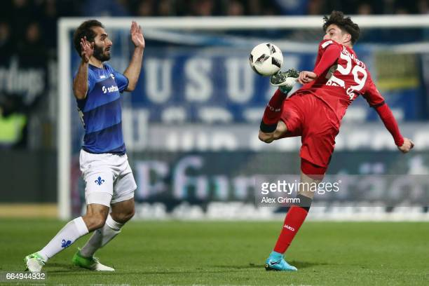 Kai Havertz of Leverkusen is challenged by Hamit Altintop of Darmstadt during the Bundesliga match between SV Darmstadt 98 and Bayer 04 Leverkusen at...