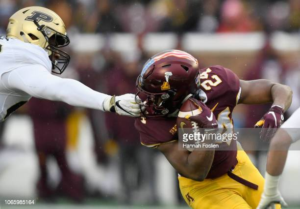 Kai Higgins of the Purdue Boilermakers grabs the facemask of Mohamed Ibrahim of the Minnesota Golden Gophers during the second quarter at TCFBank...