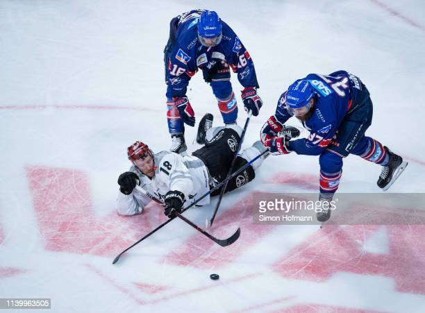 Kai Hospelt of Koeln is challenged by Thomas Larkin and Markus Eisenschmid of Mannheim during game one of the DEL PlayOffs Semi Final between Adler...