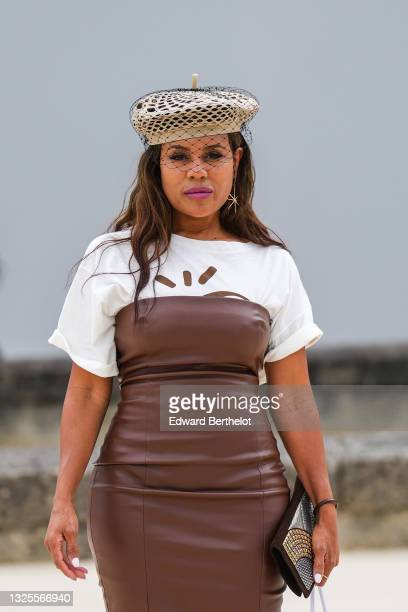 Kai Millard Morris @kaimilla wears a beige mesh with black lace Christian Dior beret / hat, a gold and silver earring, a white with brown pattern...