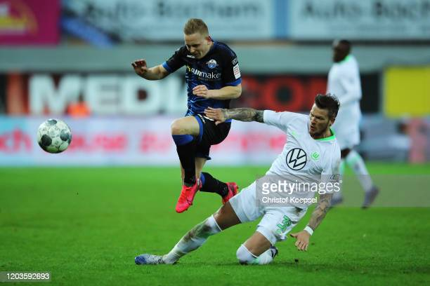 Kai Proger of SC Paderborn is tackled by Daniel Ginczek of VfL Wolfsburg during the Bundesliga match between SC Paderborn 07 and VfL Wolfsburg at...