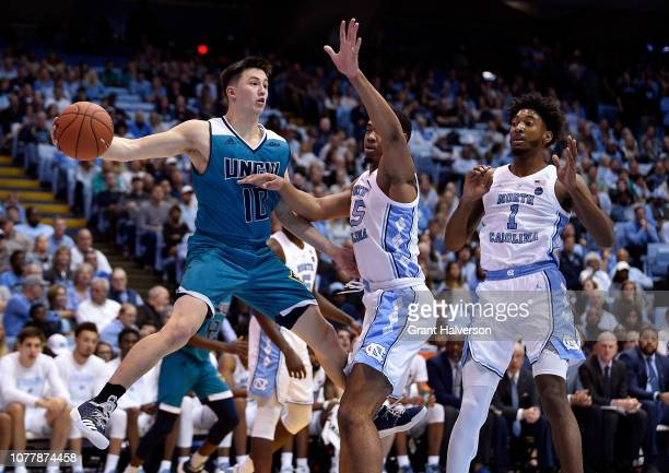 Kai Toews of the North CarolinaWilmington Seahawks looks to pass as he drives against Garrison Brooks of the North Carolina Tar Heels during the...